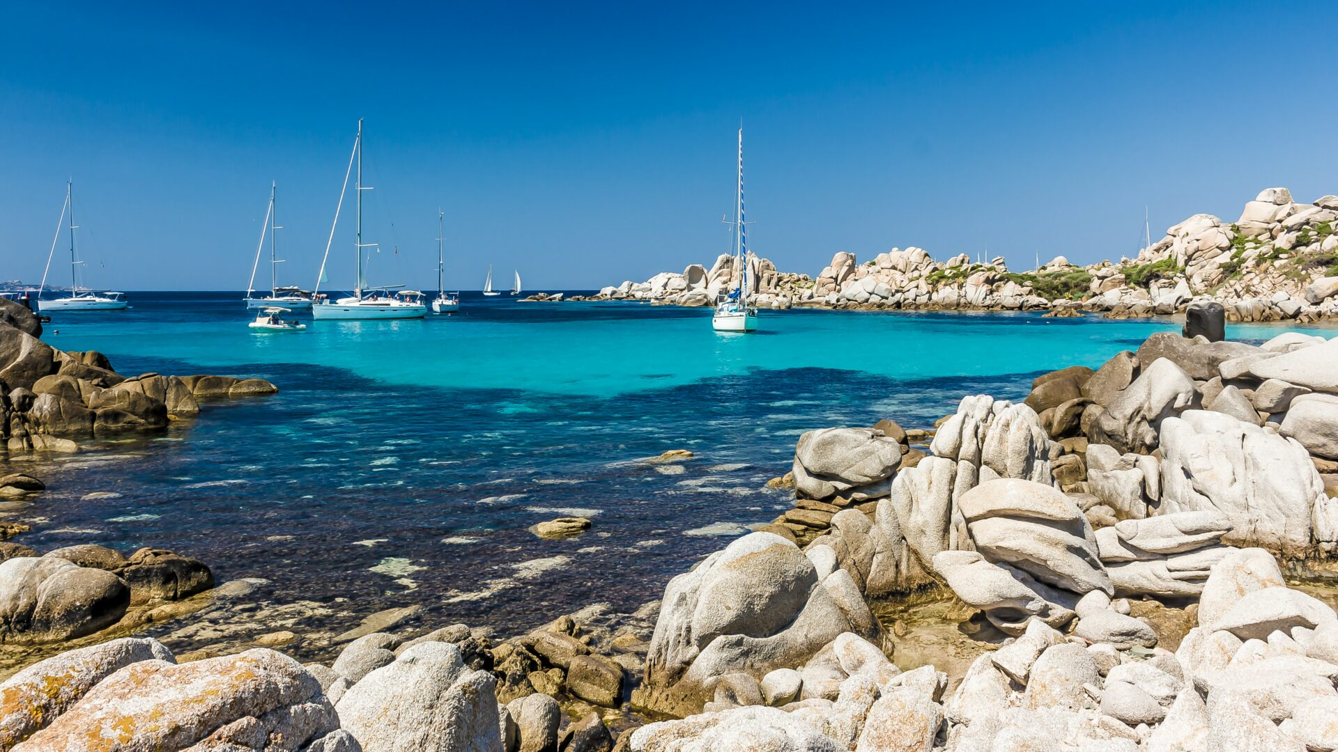 Photo of sailing boats anchored in a small cove in Corsica with beautiful clear water