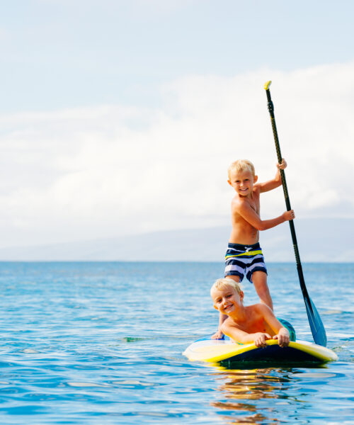 children having fun on paddle board
