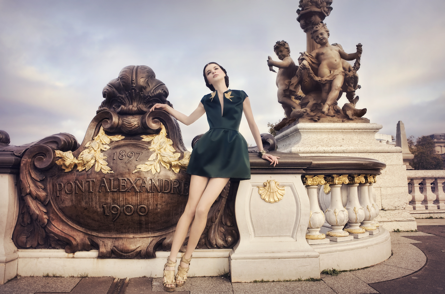 A young woman dressed in a haute couture dress posing on the Pont Alexandre 3 bridge in Paris