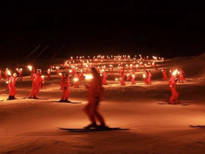 "Skiers coming down a mountain at night with lit torches ""Descente en flambeaux"""