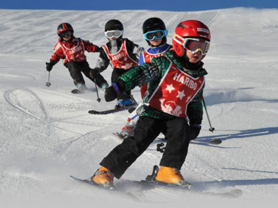 Kids skiing down a slope following each other
