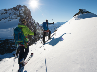A couple of persons going reaching a mountain summit with sealskins attached to their skis