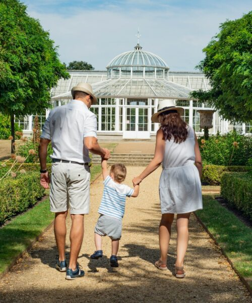 Parents hold hands with child as they visit a garden