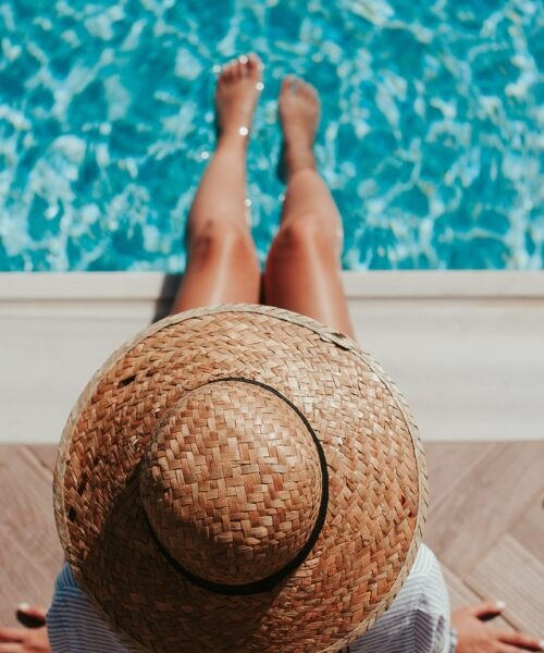 A woman wearing a straw hat with her feet in the water of a swimming pool seen from above