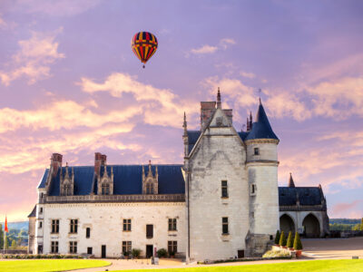 hot air balloon hovering over a chateau in the Loire Valley