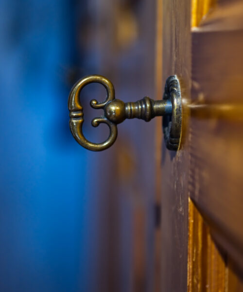 Old and mysterious key in a key hole of an old door