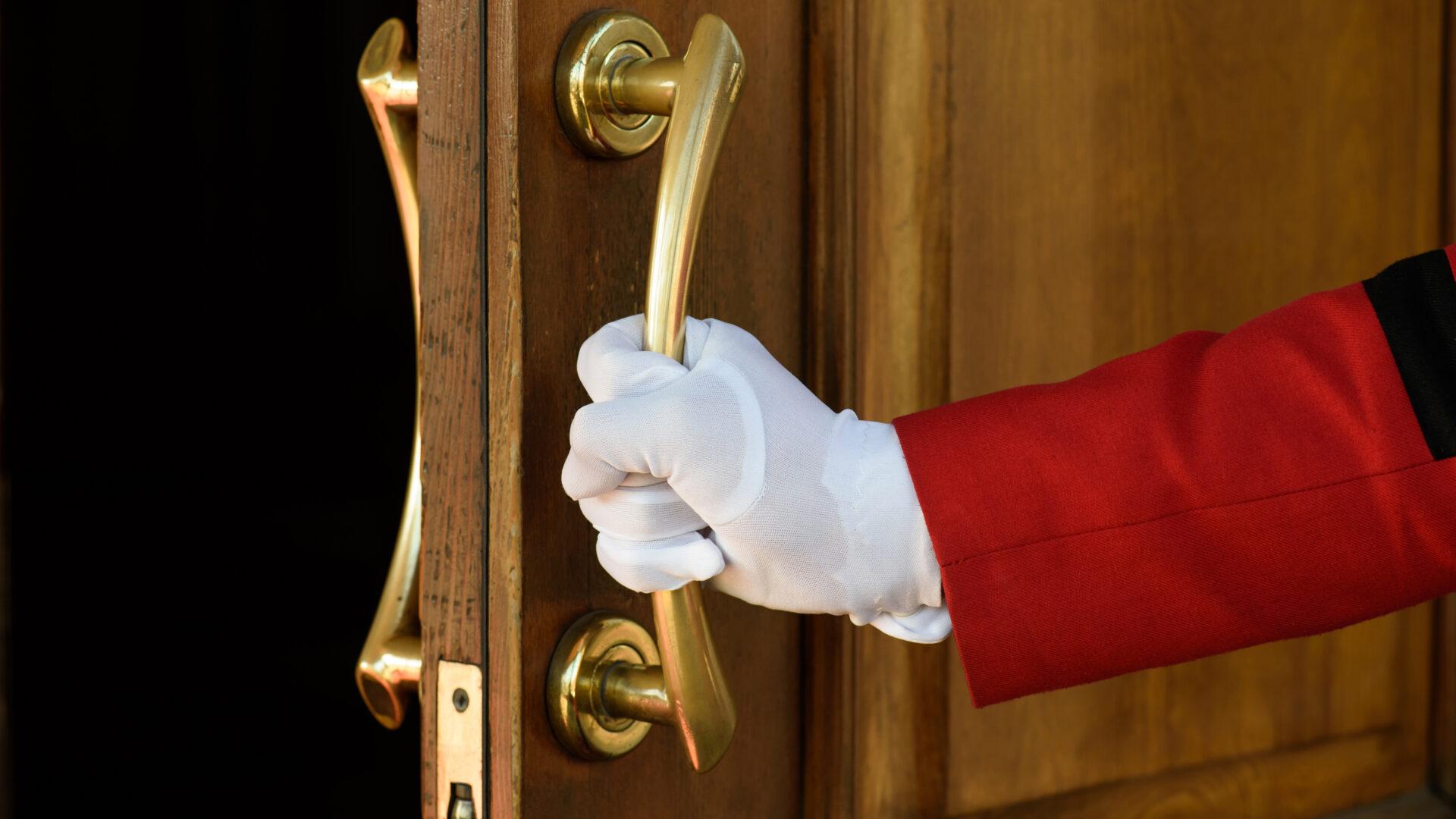 Doorman opens door for clients with white gloves