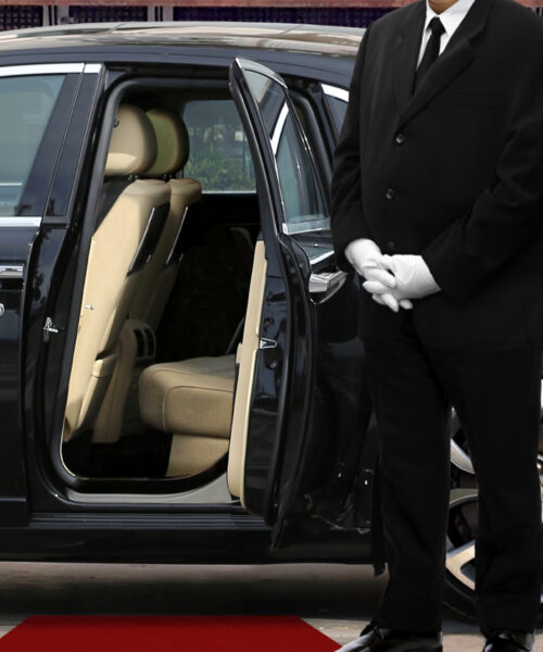 Private chauffeur waiting for guests in front of luxury vehicle