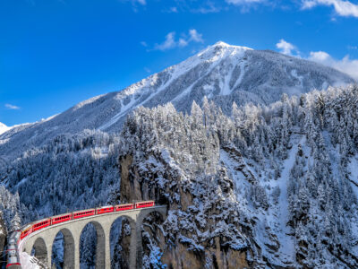 train running from one mountain to another with snow cap mountain