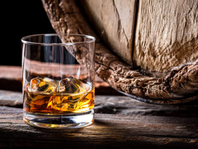 A glass of whisky in front of an old barrel