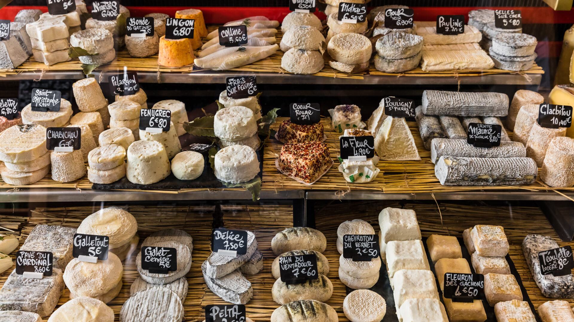A cheese presentation with lots of varieties on a market stand